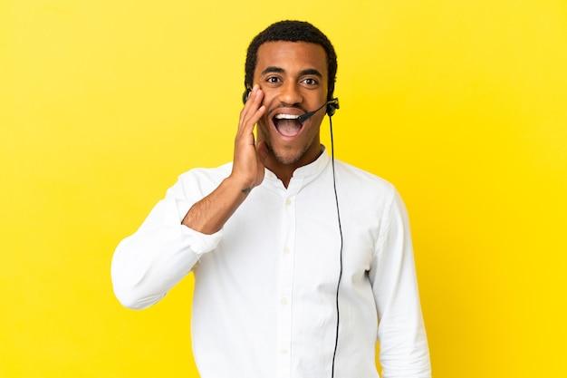 Афро-американский телемаркетер, работающий с гарнитурой на изолированном желтом фоне, с удивлением и шокированным выражением лица
