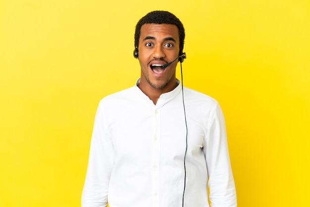 驚きの表情で孤立した黄色の背景の上にヘッドセットで作業しているアフリカ系アメリカ人のテレマーケティングの男