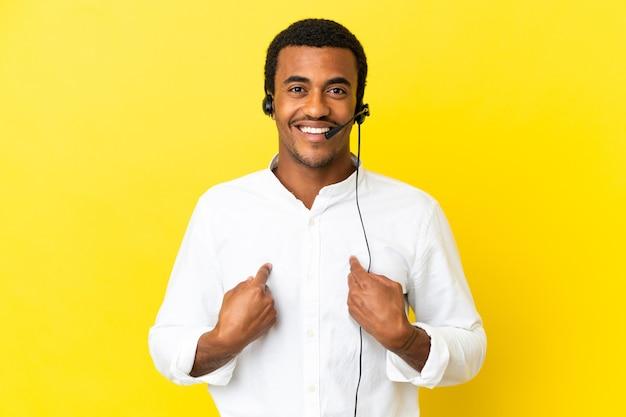 놀란 표정으로 고립된 노란색 배경 위에 헤드셋을 사용하는 아프리카계 미국인 텔레마케터