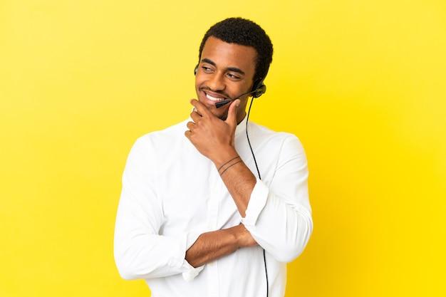 측면을 찾고 고립 된 노란색 표면에 헤드셋 작업 아프리카 계 미국인 텔레마케터 남자