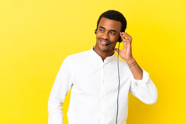 찾고있는 동안 아이디어를 생각하는 고립 된 노란색 표면에 헤드셋으로 작업하는 아프리카 계 미국인 텔레마케터 남자