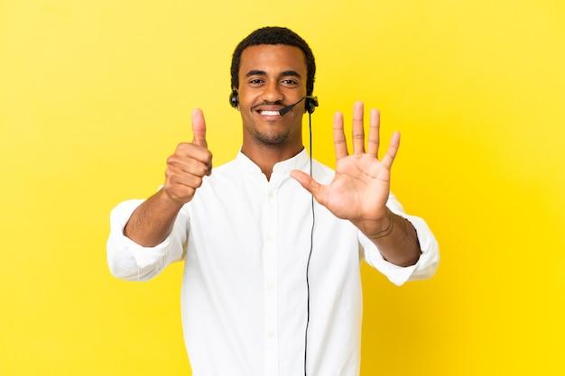 아프리카 계 미국인 텔레마케터 남자는 손가락으로 6을 세는 고립 된 노란색 벽 위에 헤드셋으로 작업