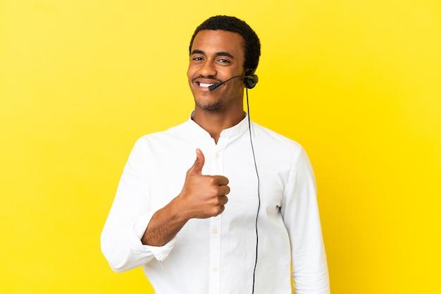 제스처를 엄지 손가락을주는 고립 된 노란색 벽 위에 헤드셋을 사용하는 아프리카 계 미국인 텔레마케터 남자