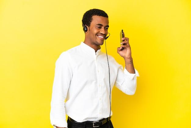 아프리카 계 미국인 텔레마케터 남자는 휴대 전화와 대화를 유지하는 고립 된 노란색 벽을 통해 헤드셋으로 작업