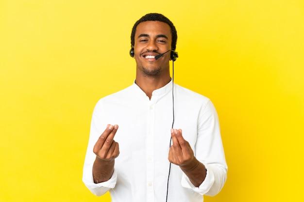 돈 제스처를 만드는 고립 된 노란색 벽 위에 헤드셋으로 작업하는 아프리카 계 미국인 텔레마케터 남자