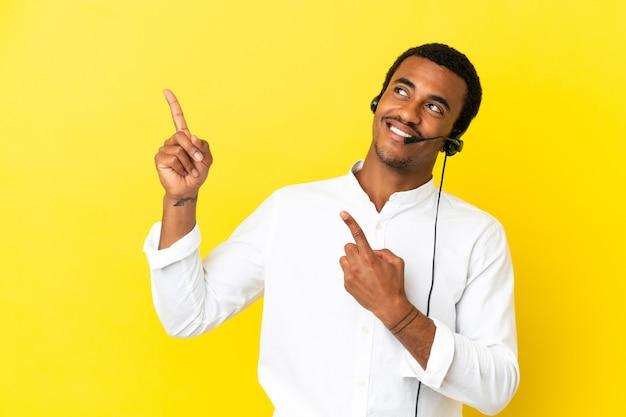 검지 손가락으로 가리키는 격리 된 노란색 벽을 통해 헤드셋으로 작업하는 아프리카 계 미국인 텔레마케터 남자 좋은 아이디어