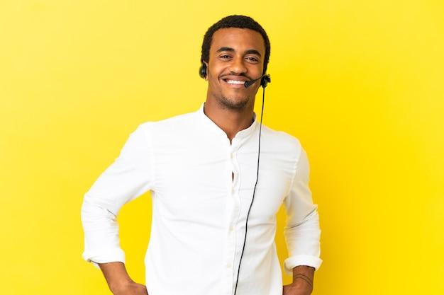 아프리카 계 미국인 텔레마케터 남자 엉덩이에 팔을 포즈와 미소 격리 된 노란색 벽 위에 헤드셋으로 작업