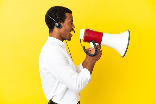 확성기를 통해 외치는 고립 된 노란색 벽을 통해 헤드셋으로 작업하는 아프리카 계 미국인 텔레마케터 남자