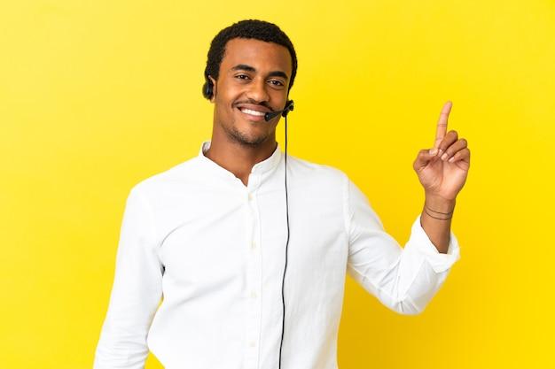 아프리카 계 미국인 텔레마케터 남자는 고립 된 노란색 벽을 통해 헤드셋으로 작업하고 최고의 기호에 손가락을 들고