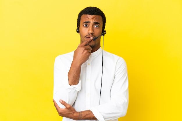 격리 된 노란색 벽을 통해 헤드셋으로 작업하는 아프리카 계 미국인 텔레마케터 남자는 오른쪽을 보면서 놀라고 충격을 받았습니다.