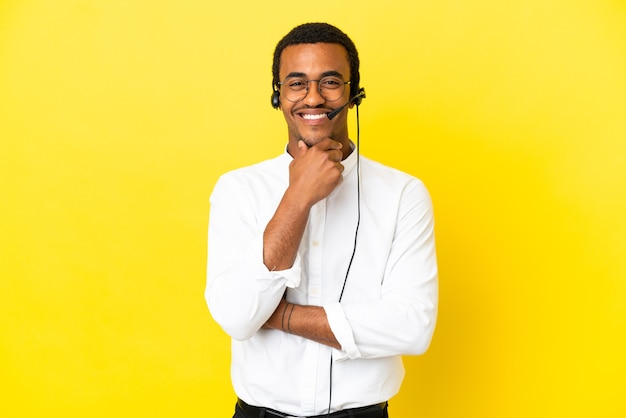 African american telemarketer man working with a headset over isolated yellow background with glasses and happy
