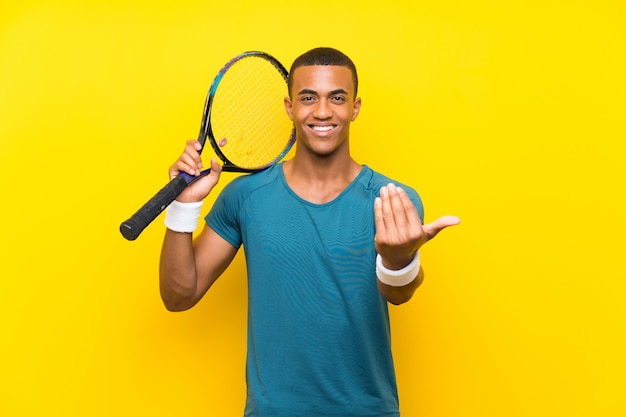 African american tennis player man inviting to come with hand. happy that you came