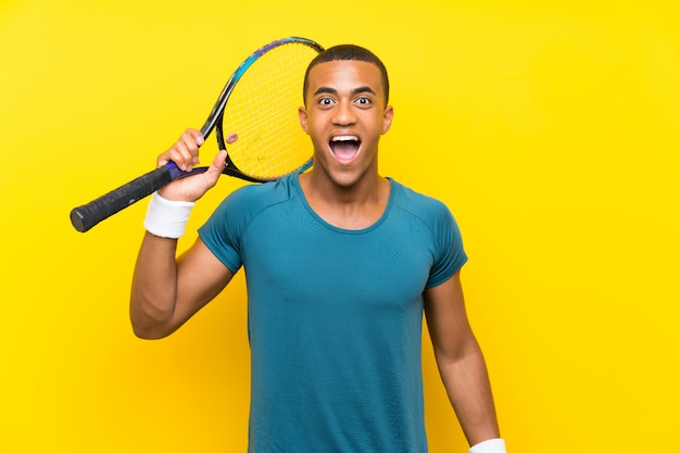 African american tennis player man with surprise and shocked facial expression
