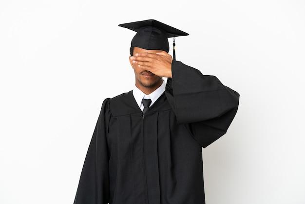 Афро-американский выпускник университета человек на изолированном белом фоне, закрывая глаза руками. не хочу что-то видеть