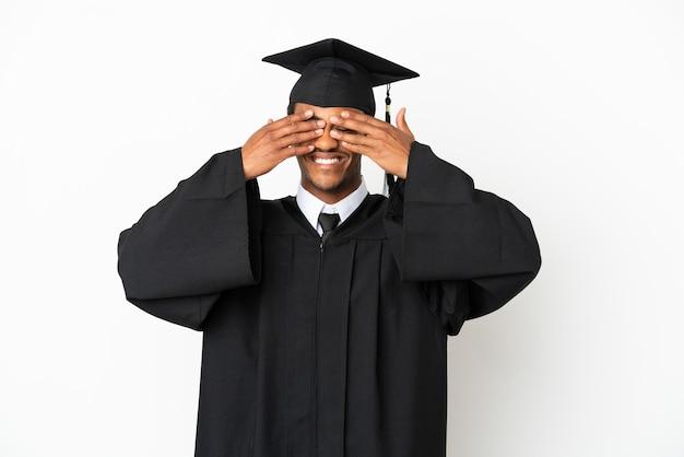 Афро-американский выпускник университета на изолированном белом фоне, закрывая глаза руками