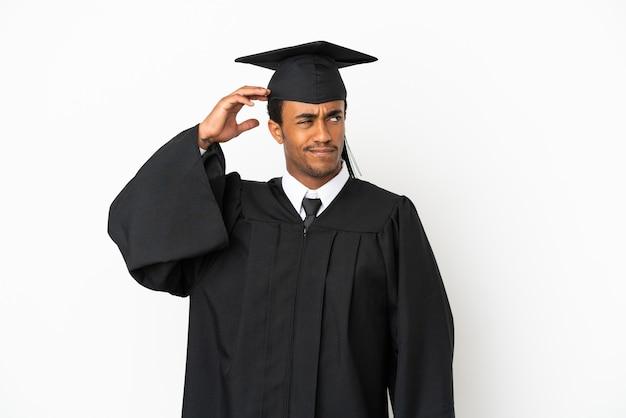 Афро-американский выпускник университета на изолированном белом фоне с сомнениями и смущенным выражением лица