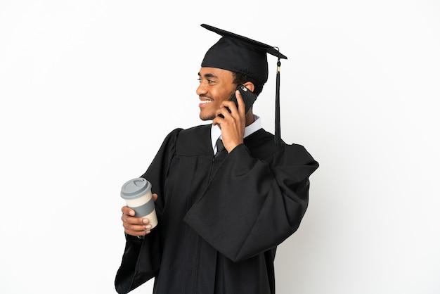 Афро-американский выпускник университета на изолированном белом фоне держит кофе на вынос и мобильный