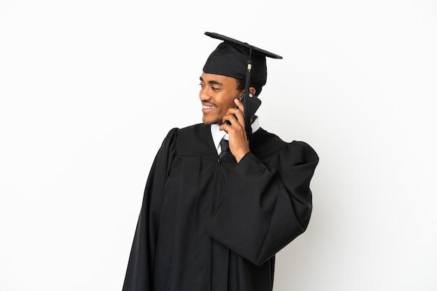 Афро-американский выпускник университета на изолированном белом фоне, разговаривая с кем-то по мобильному телефону