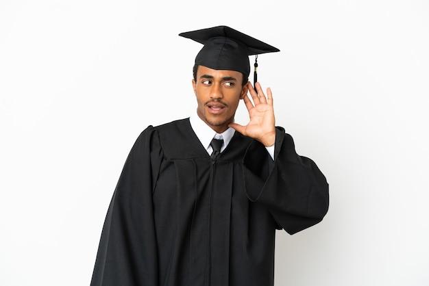 Афро-американский выпускник университета на изолированном белом фоне слушает что-то, положив руку на ухо