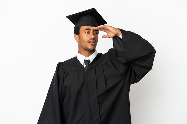 Афро-американский выпускник университета на изолированном белом фоне смотрит вдаль рукой, чтобы что-то посмотреть