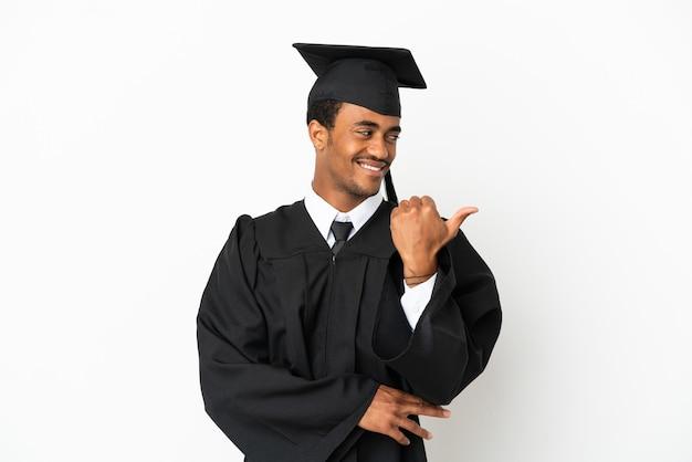 Афро-американский выпускник университета на изолированном белом фоне, указывая в сторону, чтобы представить продукт