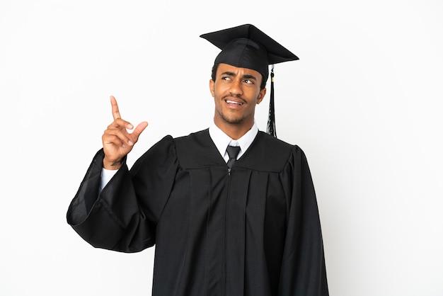 Афро-американский выпускник университета на изолированном белом фоне указывая вверх и удивлен
