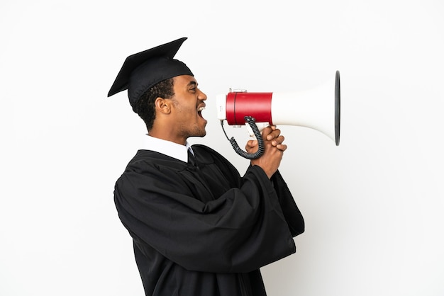 Афро-американский выпускник университета на изолированном белом фоне кричит в мегафон Premium Фотографии