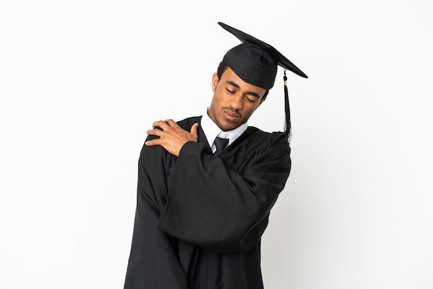 Афро-американский выпускник университета на изолированном белом фоне страдает от боли в плече за то, что приложил усилия