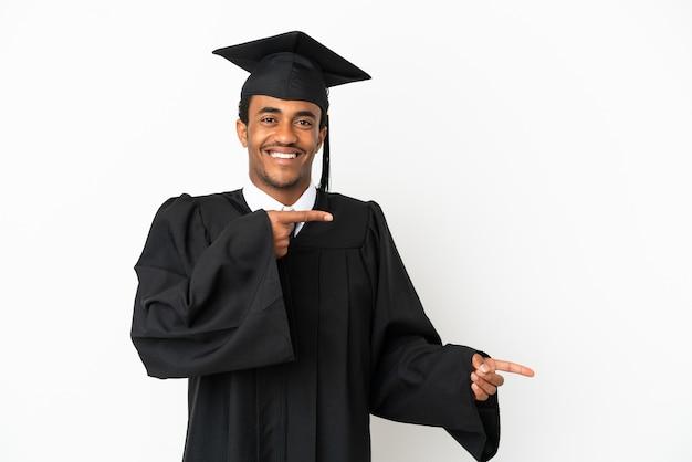 Афро-американский выпускник университета на изолированном белом фоне удивлен и указывает сторону