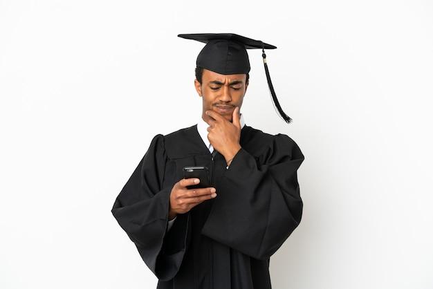 격리된 흰색 배경 위에 생각하고 메시지를 보내는 아프리카계 미국인 대학 대학원 남자