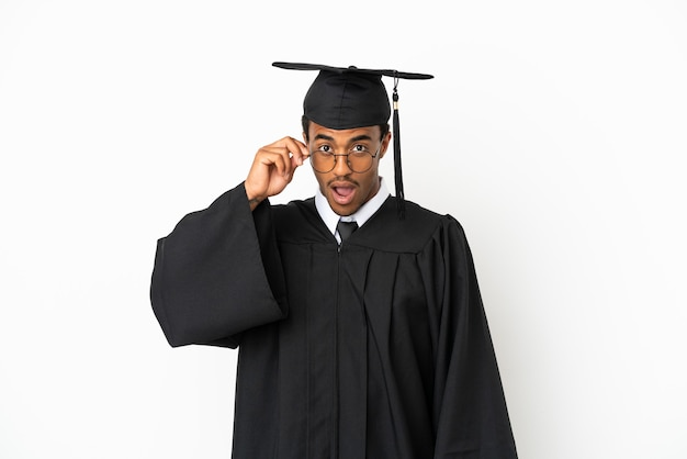 Афро-американский выпускник университета на изолированном белом фоне в очках и удивлен