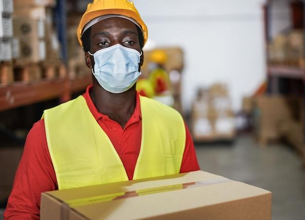 コロナウイルスの安全フェイスマスクを着用しながらパッケージを保持しているアフリカ系アメリカ人の倉庫作業員