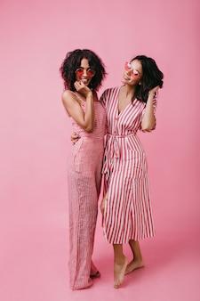 Afro-americano con i capelli ricci dall'aspetto carino. le ragazze in abiti estivi a strisce godono di un servizio fotografico.