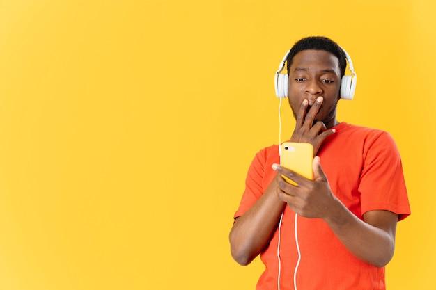 ヘッドフォン音楽技術黄色の背景を持つアフリカ系アメリカ人