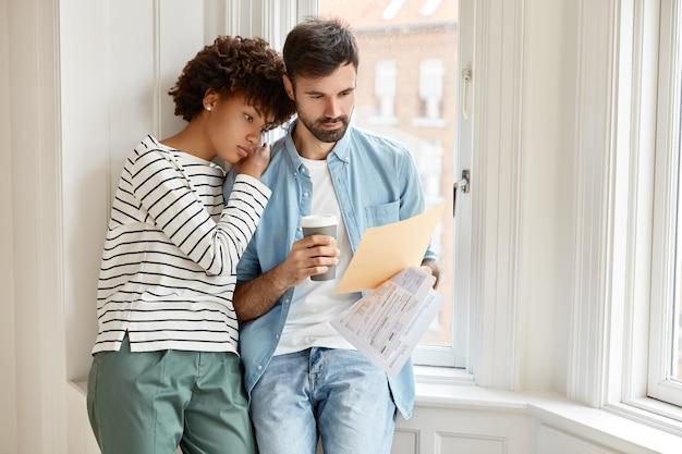 아프리카 계 미국인 여성과 수염을 기른 코카서스 인 남편이 직원과 새 계약 조건을 논의합니다.