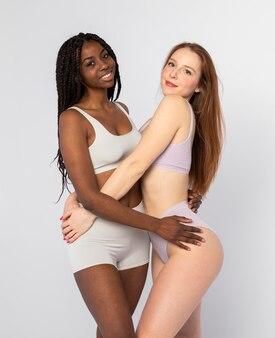 Афро-американская женщина и рыжая женщина позирует вместе