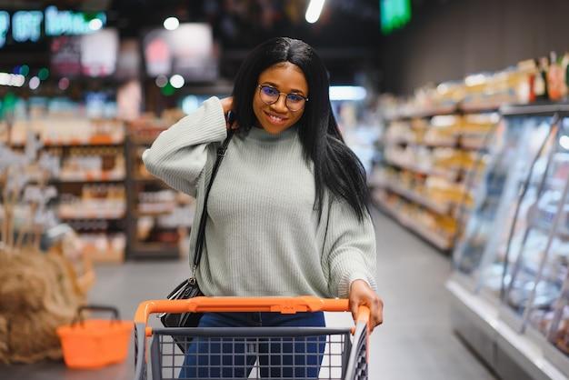 쇼핑 카트 슈퍼마켓에서 아프리카 계 미국인 여자입니다.