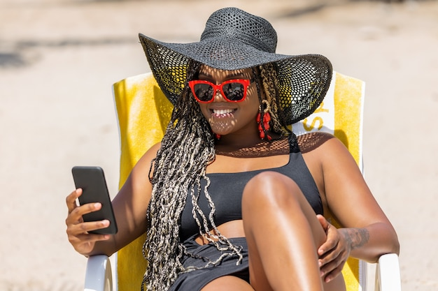 African-american woman on the beach using phone relaxing in deck chair wearing a black hat and sunglasses. cheerful adult woman enjoying a summer day at the beach.