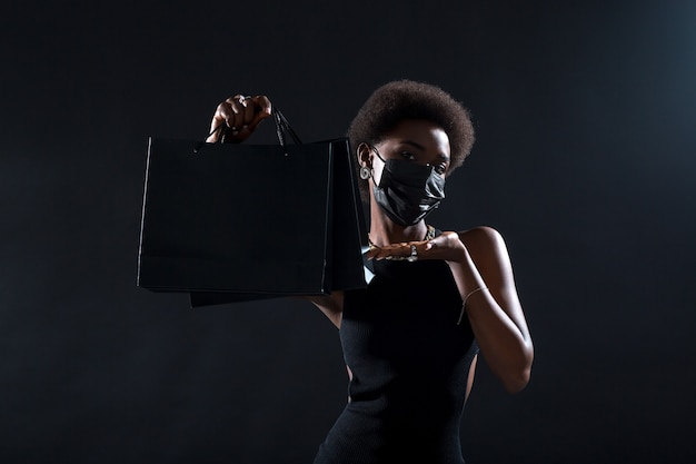 African american woman in black medical face mask holds black shopping bags. safety on black friday concept. covid-19 coronavirus protection.