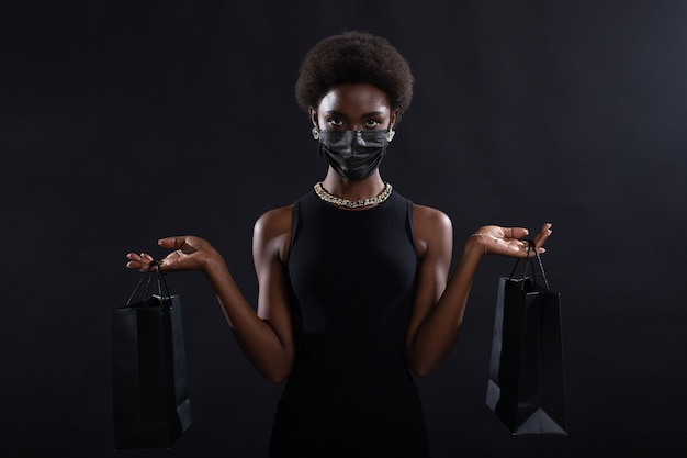 African american woman in black medical face mask holds black shopping bags safety on black friday concept covid coronavirus protection