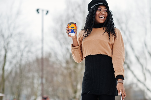 African american woman in black skirt, brown sweater and cap posed at winter day against snowy background, holding cup of coffee