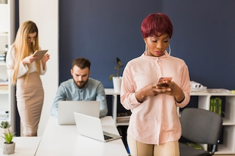 African-American woman browsing smartphone in office