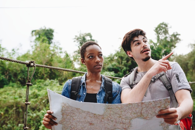 African american woman and a caucasian man looking at a map together travel and teamwork concept