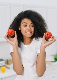 아프리카 계 미국인 여자는 부엌에 서있는 두 토마토 사이 선택. 건강한 라이프 스타일 개념, 채식, 다이어트