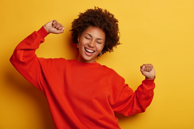 African american woman dances happily laughing isolated