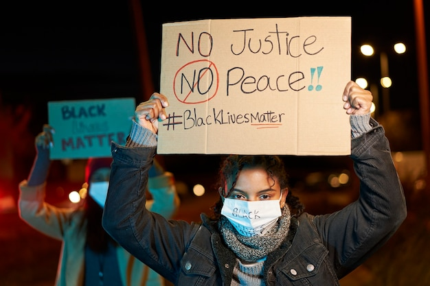 African-american woman demonstrating against racism, holding a banner. demonstrators in a city with banners fighting for their rights. black lives matter.