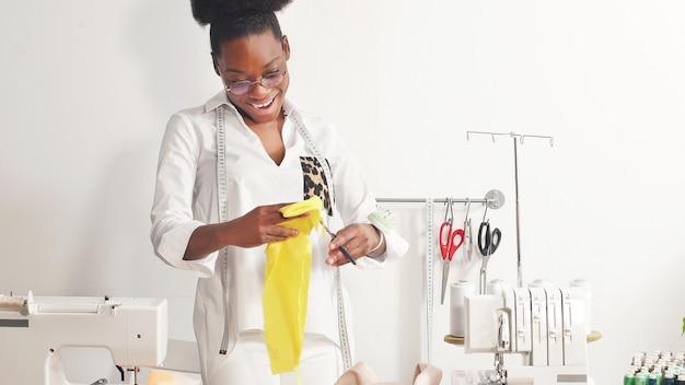 Афро-американская портниха работает на своей любимой работе и шьет одежду в своей швейной мастерской.