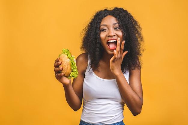 ハンバーガーを食べるアフリカ系アメリカ人の女性