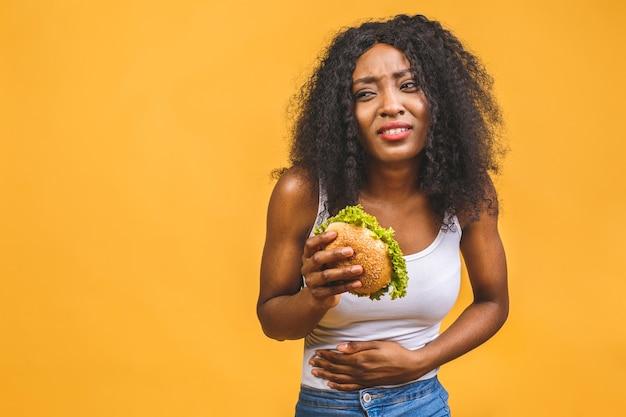 Афро-американская женщина ест гамбургер