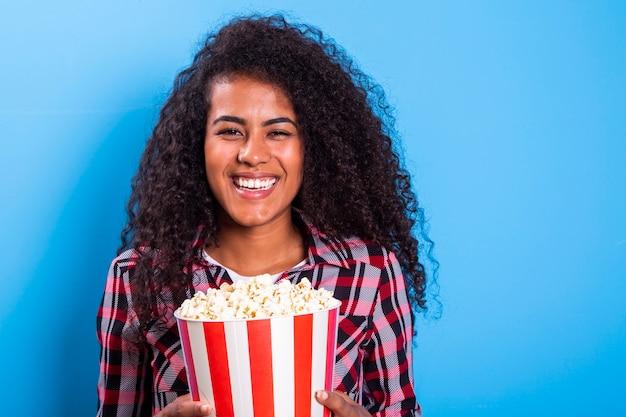 큰 웃음과 함께 행복 한 팝콘을 먹는 아프리카 계 미국인 여자